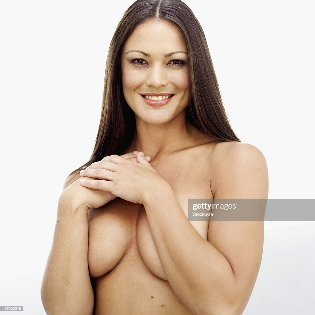 Portrait of a young nude woman covering her breasts with her arms : Stock Photo