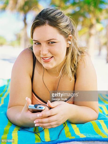 portrait of a young overweight woman sunbathing, listening to music - fat woman at beach stock photos and pictures