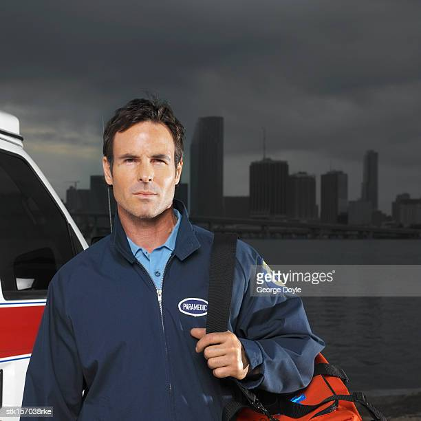 portrait of a young paramedic standing beside an ambulance