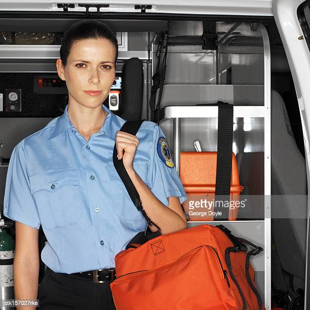 portrait of a young paramedic standing inside an ambulance