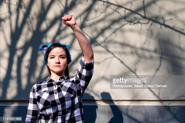 portrait of a young, powerful, beautiful activist woman wearing a bandana raising her fist in the air. - demonstrant stock-fotos und bilder