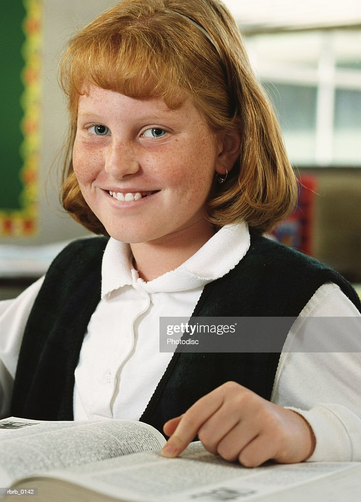 portrait of a young redheaded girl as she sits and smiles at her desk in her classroom : Stockfoto