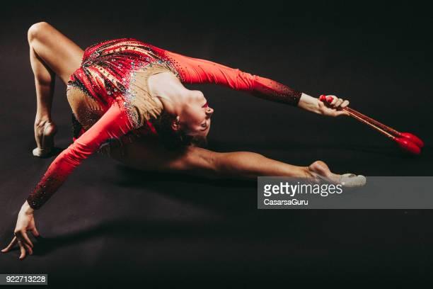 porträt eines jungen rhythmische sportgymnastik athleten auf schwarzem hintergrund - rhythmic gymnastics stock-fotos und bilder