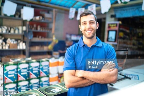 portrait of a young sales man standing in a paint store - salesman stock pictures, royalty-free photos & images
