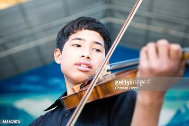 Portrait of a young school boy playing his violin fully concentrated on his hands