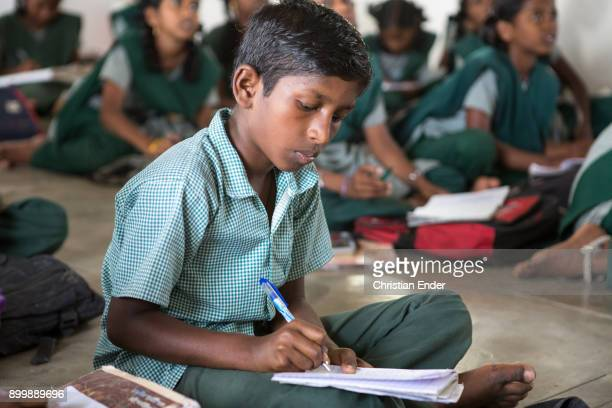 Portrait of a young school boy writing down notes inside his class room while lesson.