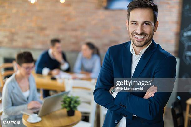 portrait of a young smiling businessman with arms crossed - focus on foreground stock pictures, royalty-free photos & images