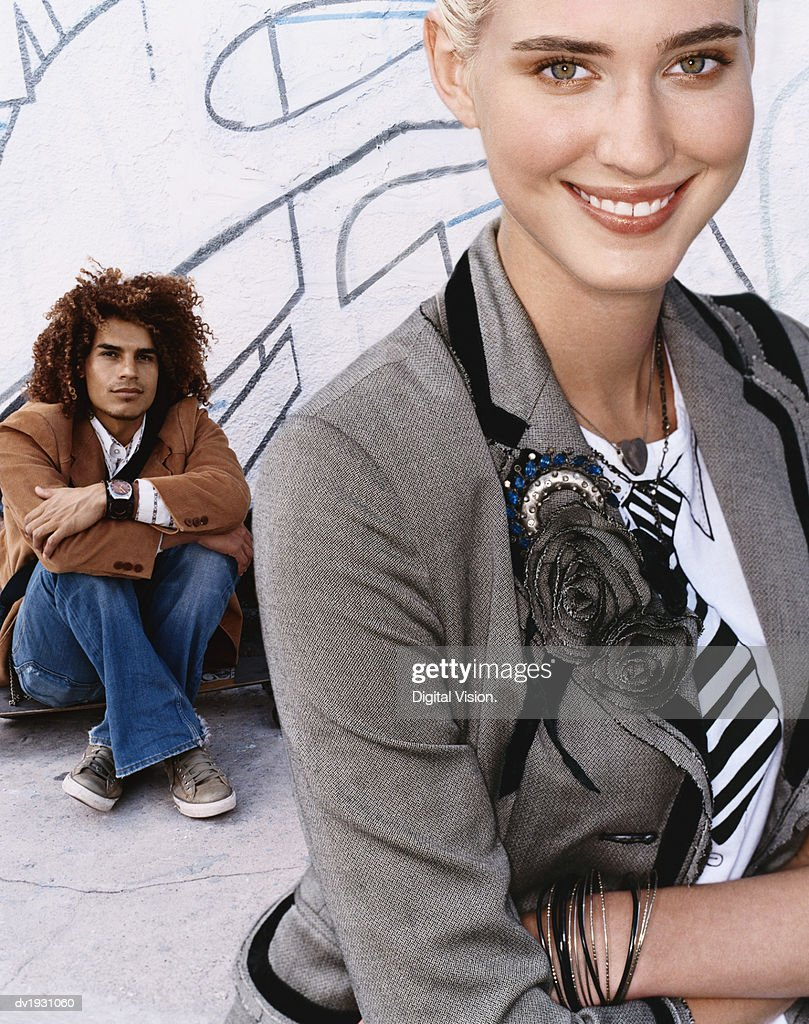 Portrait of a Young, Smiling Woman Standing in Front of a Young Man Sitting Against a Wall : Stock Photo