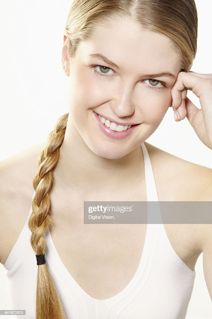 Portrait of a Young, Smiling Woman With Her Hand on Her Head : Stock Photo