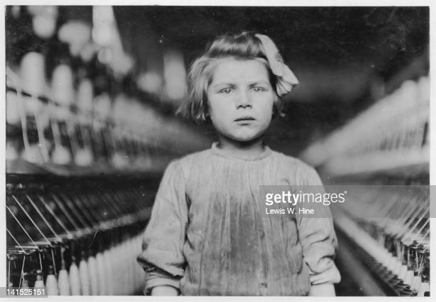 Portrait of a young spinner in a cotton mill, August, Georgia, 1909. A spinner's job was to continually walk along the aisles of spinning machines,...