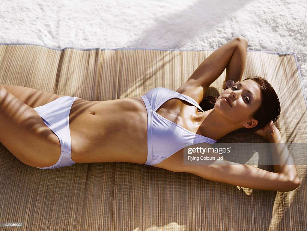 Portrait of a Young, Tanned Woman in a Bikini Lying on a Mat on the Beach : Stock Photo