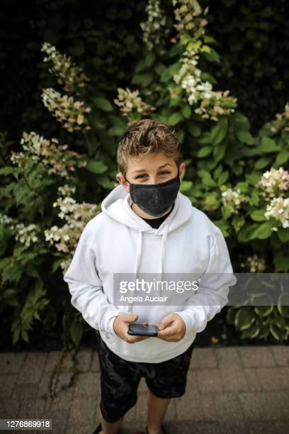portrait of a young teen boy wearing protective face mask - angela auclair stock pictures, royalty-free photos & images