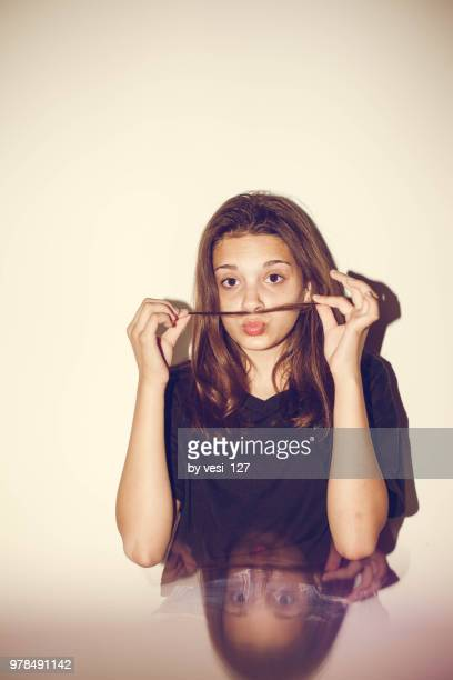 Portrait of a young teenage girl making mustache with hair