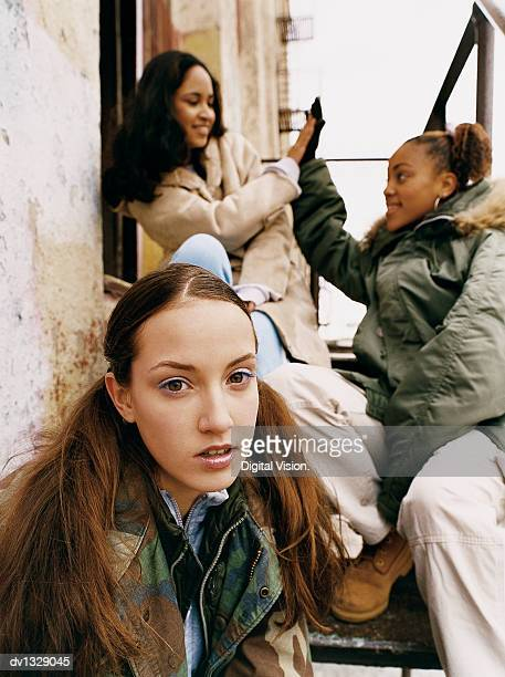 portrait of a young teenage girl sitting outdoors and her friends sitting behind on a flight of steps - chav stock photos and pictures