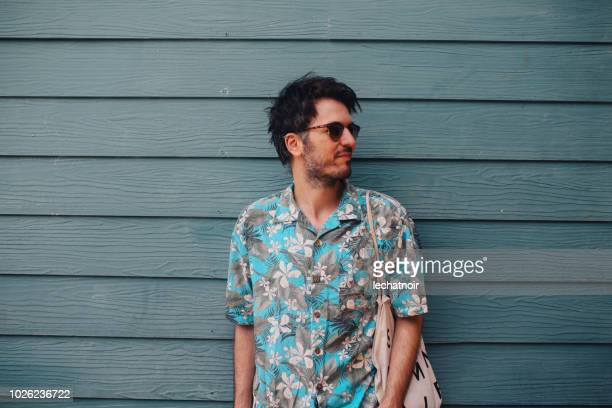 portrait of a young tourist man wearing hawaiian shirt and sunglasses - hawaiian shirt stock photos and pictures