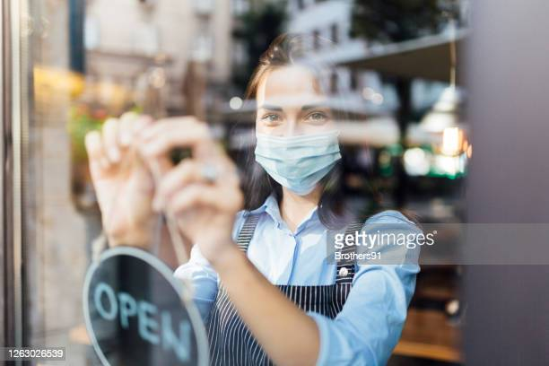 portrait of a young waitress opening a cafe - new normal concept stock pictures, royalty-free photos & images