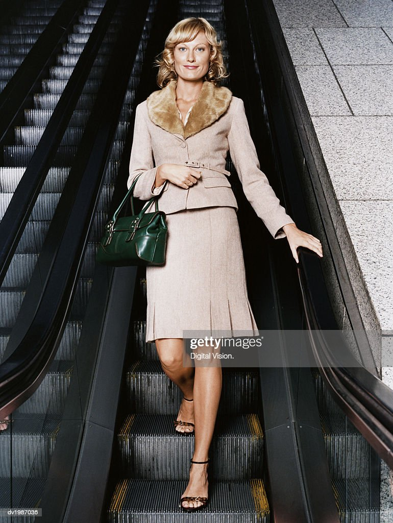 Portrait of a Young, Well Dressed Woman Standing on an Escalator : Stock Photo