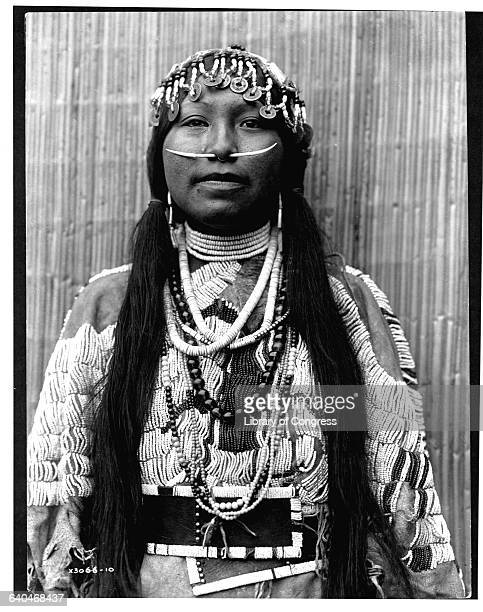 A portrait of a young Wishram woman wearing a dentalium shell nose ornament a headdress with Chinese coins and a beaded dress published in Volume...