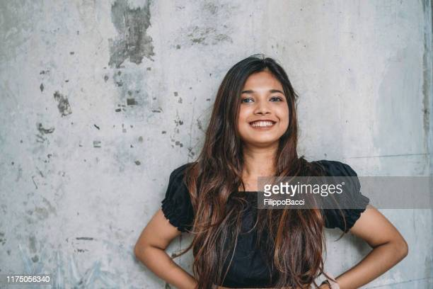 portrait of a young woman against a wall - traditionally cambodian stock pictures, royalty-free photos & images