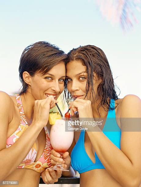 Portrait of a young woman and a mid adult woman drinking a cocktail through a straw