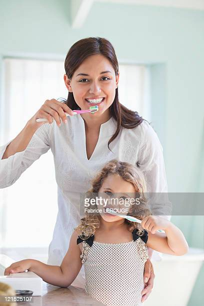 Portrait of a young woman and her daughter brushing teeth