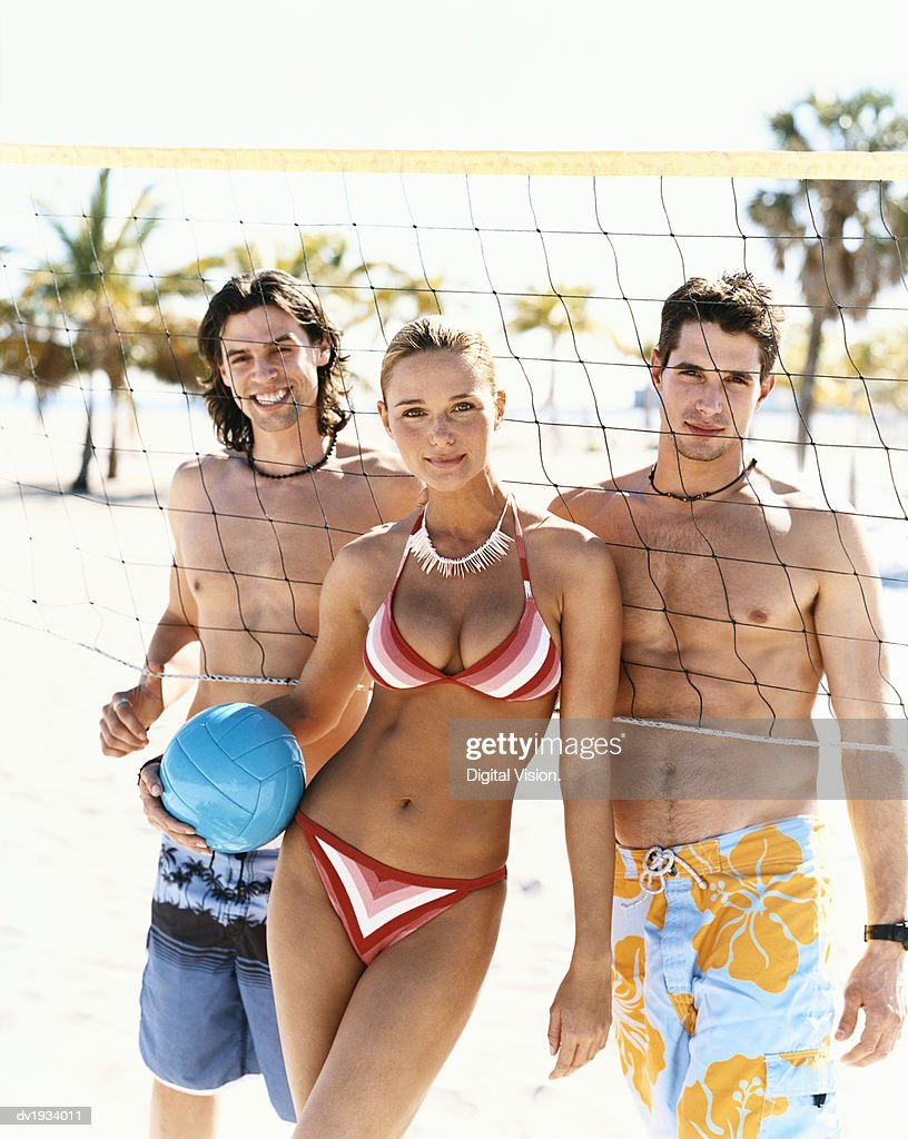 Portrait of a Young Woman and Men in Swimwear Standing by a Volleyball Net : Stock Photo