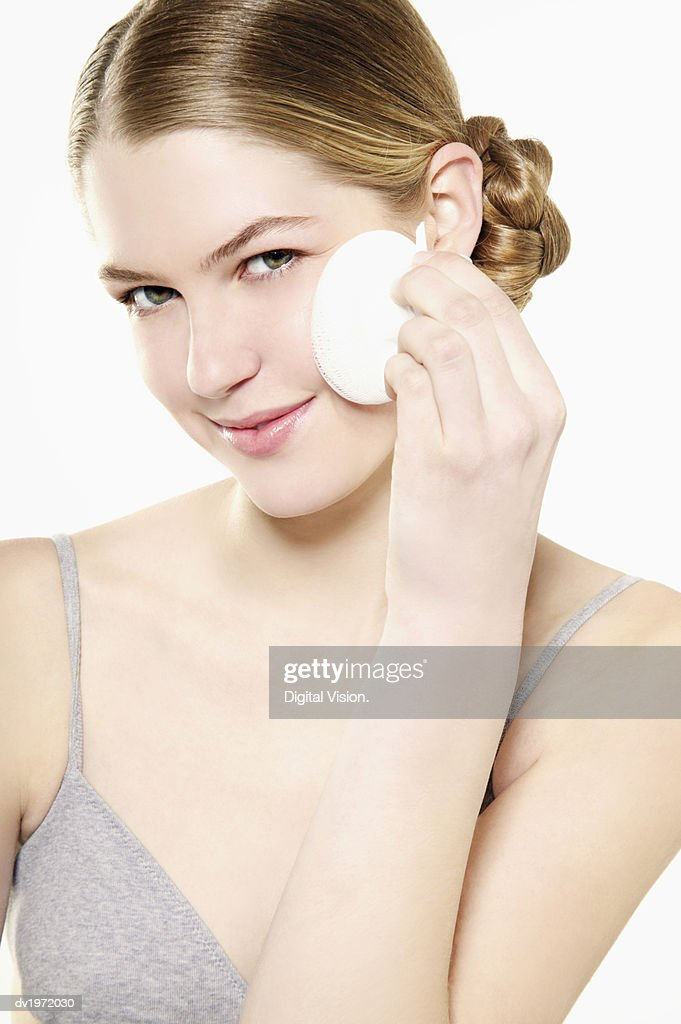 Portrait of a Young Woman Applying Foundation : Stock Photo