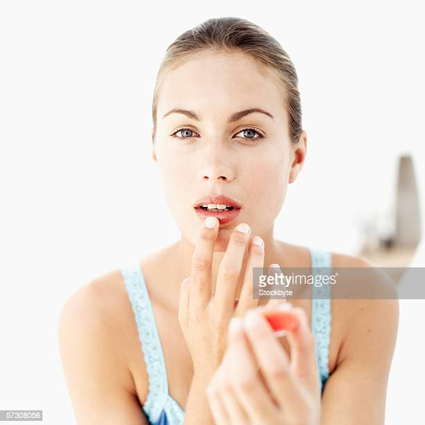 portrait of a young woman applying lip gloss - lip balm stock pictures, royalty-free photos & images