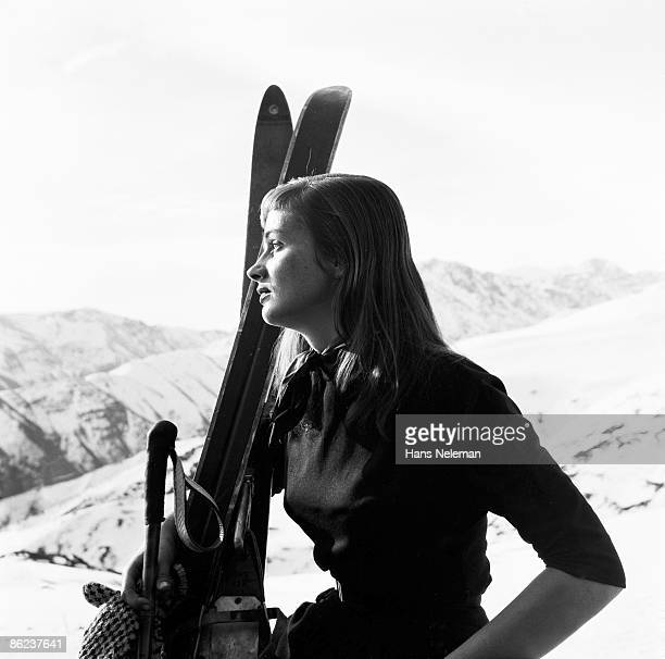 Portrait of a young woman as she poses with skis and poles against a snowy, mountainous backdrop, Santiago, Santiago Region, Chile, June 1950.