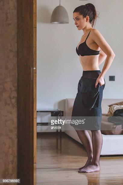 porträt einer jungen frau zu hause anziehen und die vorbereitung für eine arbeit - junge frau strumpfhose stock-fotos und bilder