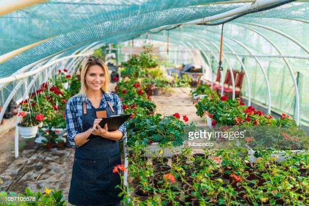 Portrait of a young woman at work in greenhouse