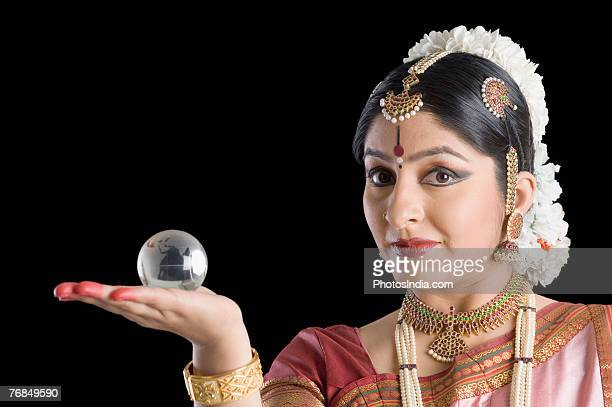 Portrait of a young woman balancing a glass globe