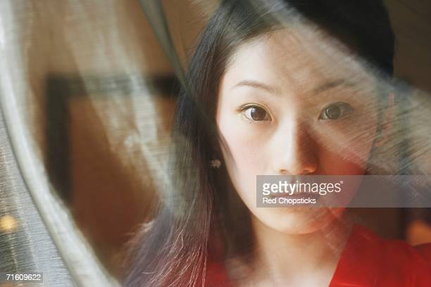 Portrait of a young woman behind a curtain