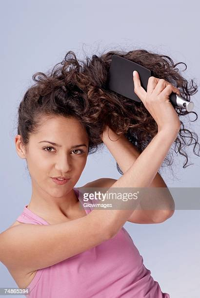 Portrait of a young woman brushing her hair