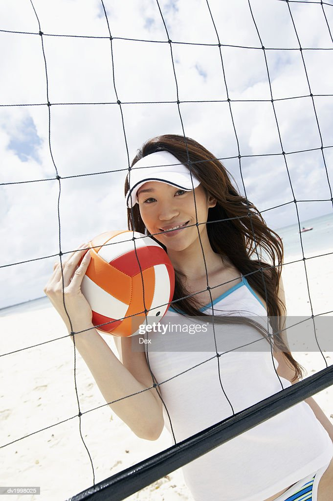 Portrait of a Young Woman by a Volleyball Net on the Beach : Stock Photo