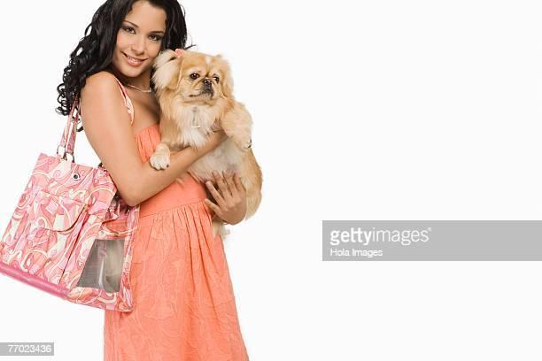 portrait of a young woman carrying a pomeranian dog - cão fraldeiro - fotografias e filmes do acervo