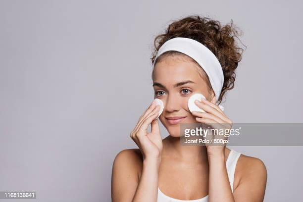 portrait of a young woman cleaning face in a studio, beauty and skin care - ヘアバンド ストックフォトと画像