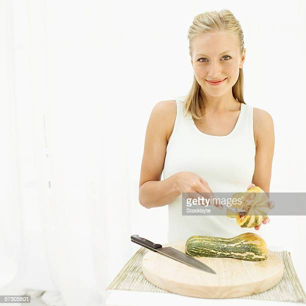 Portrait of a young woman cleaning out half a pumpkin