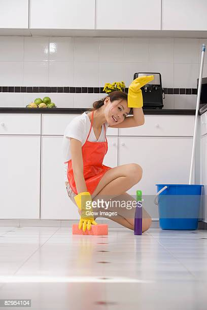 Portrait of a young woman cleaning the floor with a bath sponge