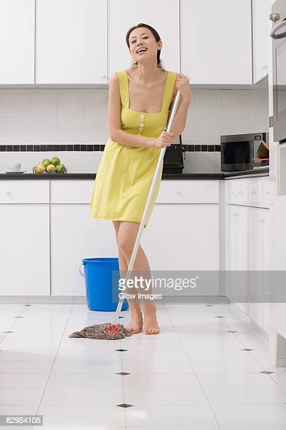 Portrait of a young woman cleaning the floor with a mop