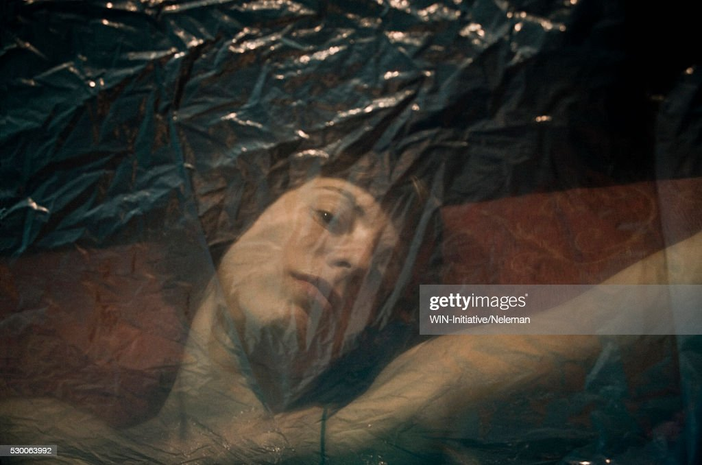 Portrait of a young woman covered with a polythene, : Stock Photo