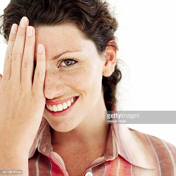 portrait of a young woman covering her face with her hand
