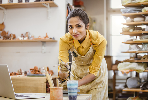 Portrait of a Young Woman Creating Pottery, Using Laptop 917649678