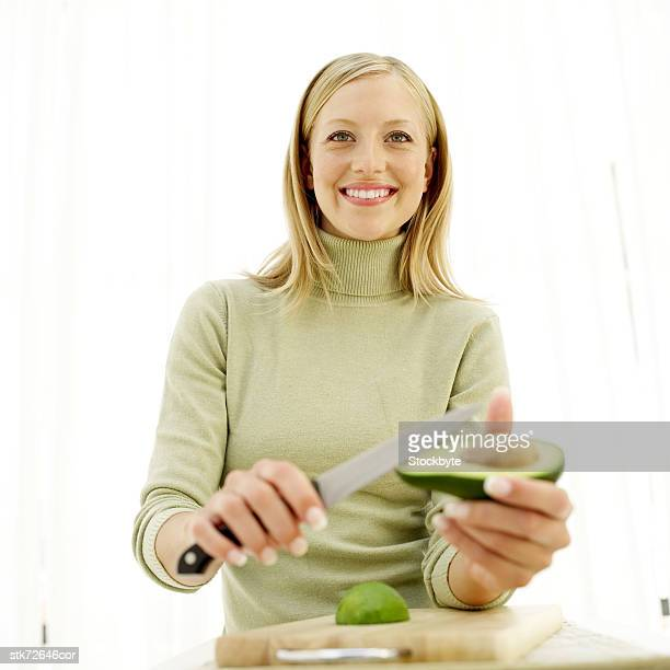 portrait of a young woman cutting an avocado