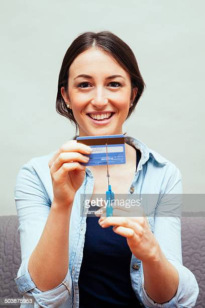 Portrait of a Young woman cutting up credit card