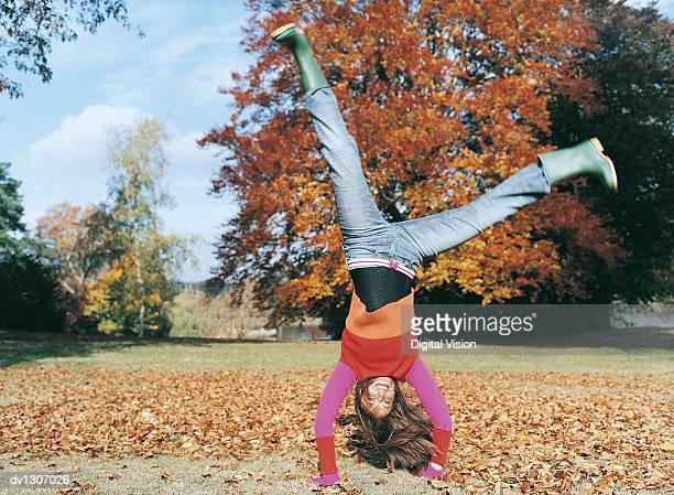 portrait of a young woman doing a cartwheel in a park - cartwheel stock pictures, royalty-free photos & images