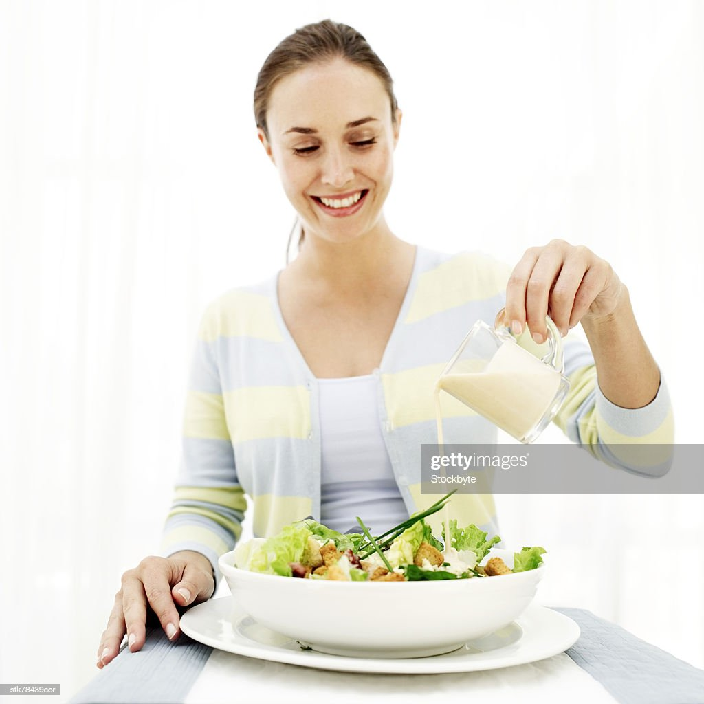 portrait of a young woman dressing a salad : Stock Photo