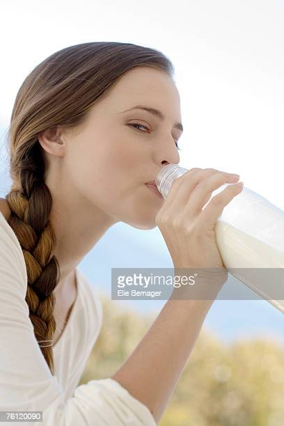 Portrait of a young woman drinking milk from the bottle, outdoors