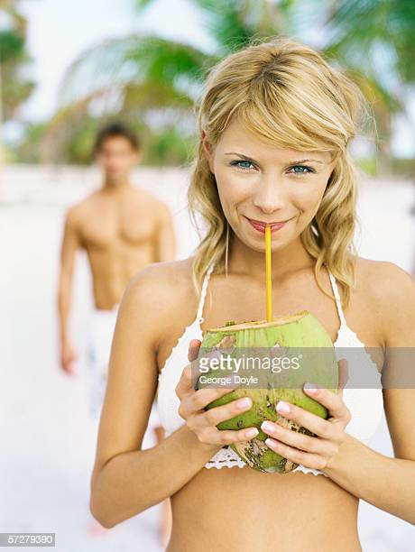 Portrait of a young woman drinking through a straw from a coconut