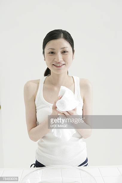 Portrait of a young woman drying her hand with a towel